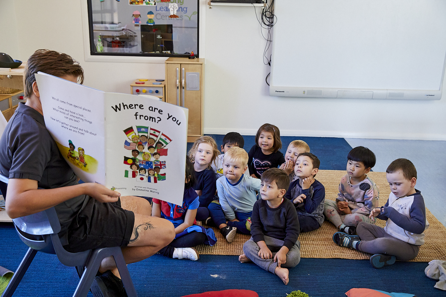 Child care educator reading to group of children in child care classroom at Papilio Dundas Valley