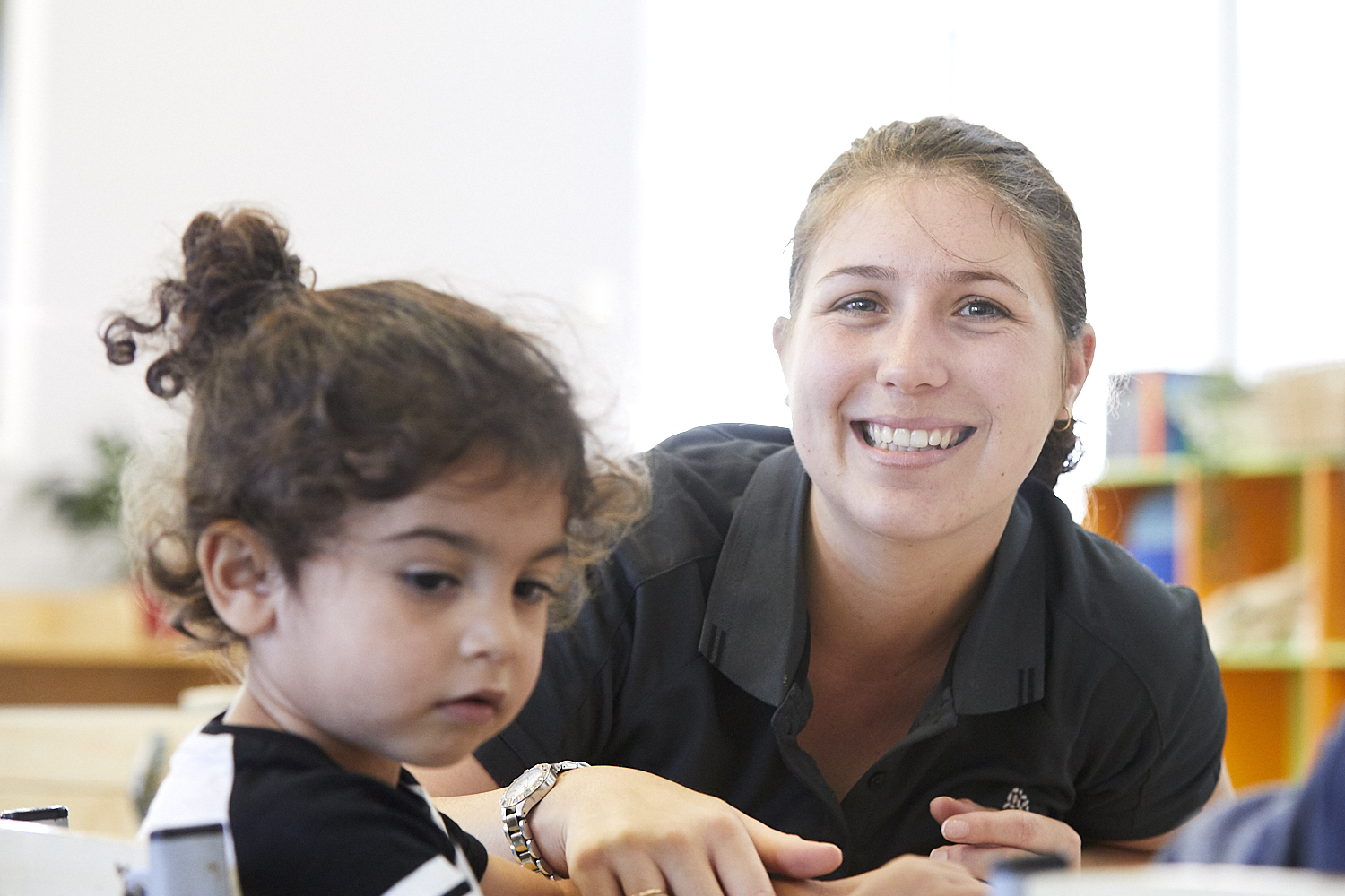 Child care educator with young child in child care classroom at Papilio Dundas Valley